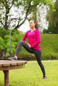 fitness, sport, training, park and lifestyle concept - smiling african american woman stretching leg