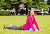 fitness, sport, training, park and lifestyle concept - smiling african american woman stretching on
