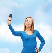 technology and internet concept - smiling woman taking self picture with smartphone camera