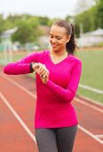 sport, fitness, technology, healthcare and people concept - smiling young woman with heart rate watc