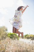 Beautiful woman in floral dress jumping up on a sunny day in the countryside