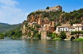 view of the Ebro River and the old town of Miravet, Spain, highlighting the Templar castle in the to