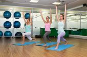 Yoga class in warrior pose in fitness studio at the leisure center