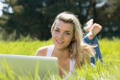 Pretty blonde lying on grass using laptop smiling at camera on a sunny day in the countryside