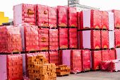 stock photo of pallet  - Red clay building bricks stacked on pallets still wrapped in their plastic for delivery at a warehouse factory or construction site - JPG