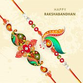Beautiful peacock feathers decorated rakhi on beige background for the occasion of Raksha Bandhan celebrations.