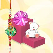Big gift boxes and teddy bears with pearls decorated rakhi on shiny yellow background for Raksha Ban