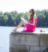 Girl reading a book in  park film effect