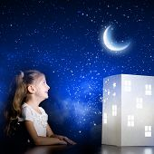 Cute little girl looking at model of house and dreaming