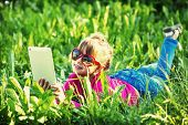 Little girl with a tablet PC lying in the grass on park (film style photography)
