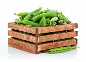 Green peas in wooden box. Isolated on white background