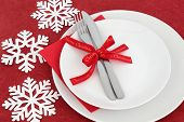 Christmas dinner place setting with white plates, red bow ribbon, cutlery and snowflake decorations