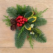 Christmas flora with holly, ivy mistletoe, fir and pine cones over oak wood background.