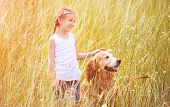 Smiling Little girl with labrador retriever in field
