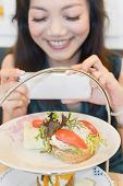 Asian woman take a picture to the dish in restaurant.