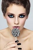 Portrait of young beautiful sexy woman with black and white striped lollipop