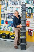 Full length of smiling senior man stacking toolboxes in hardware store