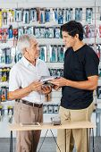 Smiling father and son buying tools in hardware store