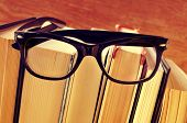 a pair of eyeglasses on a pile of books, with a retro effect