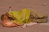 Homeless Man Sleeps On The Sidewalk Near The River Ganges In Haridwar, India.