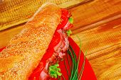 french sandwich : fresh white baguette with chicken smoked sausage over red plate on wood