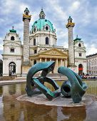 VIENNA, AUSTRIA - SEPTEMBER 26, 2013: On the square in front of church a big pond with a sculpture t
