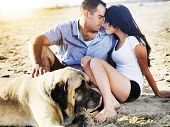 romantic couple with pet dog on the beach.
