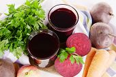 Glasses of fresh beet juice and vegetables on cutting board close up