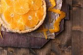 Homemade orange tart on wooden background