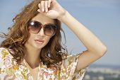 portrait of beautiful brunette girl in sunglasses on background blue sky