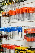 Blue and orange screwdrivers hanging in hardware shop