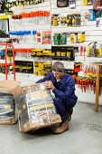 Full length of mature worker lifting tool package in hardware shop