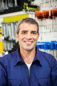 Portrait of confident worker smiling in hardware shop