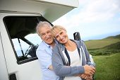 stock photo of motorhome  - Senior couple standing by motorhome in countryside - JPG