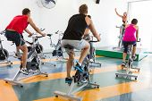 Spin class working out with motivational instructor at the gym