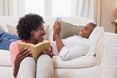 Cute couple relaxing reading book and using smartphone at home in the living room