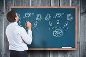 Thinking businessman holding pen against blackboard with technology doodles