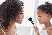 Pretty mother teaching her daughter about makeup at home in the bathroom