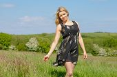 Pretty blonde in sundress smiling at camera on a sunny day in the countryside