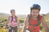Fit cyclist couple riding together on mountain trail on a sunny day