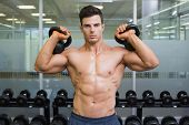 Portrait of a young muscular man lifting kettle bells in gym