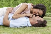 Romantic young woman touching man's lips while lying on him in park