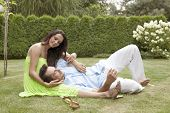 Full length of young man lying on woman's lap in park