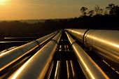 stock photo of oilfield  - pipeline connection from crude oil field during sunset