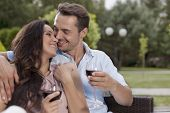 Affectionate young couple having red wine in park