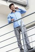 Full length of happy young businessman using mobile phone at balcony