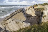 Remains of ruins of old fortification. Big concrete blocks on the seashore.