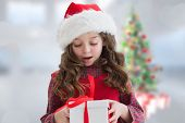 Cute girl looking at gift against blurry christmas tree in room