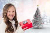 Girl holding gift against blurry christmas scene