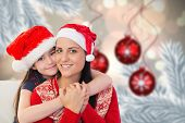 Mother and daughter against digital hanging christmas bauble decoration